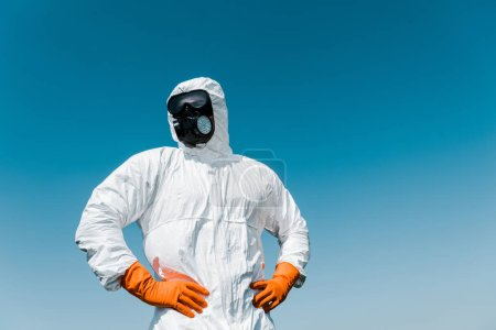 Photo pour Exterminateur en masque protecteur et uniforme debout avec les mains sur les hanches - image libre de droit
