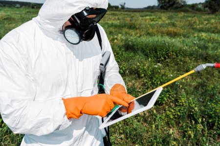 exterminator in protective mask and uniform pointing with finger at laptop