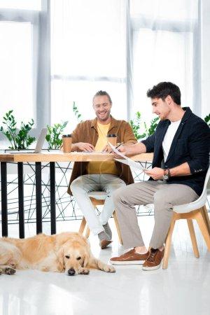 Foto de Dos amigos guapos sonriendo y haciendo papeleo en la oficina - Imagen libre de derechos