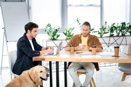 Photo pour Deux beaux amis utilisant un ordinateur portable et un smartphone dans le bureau - image libre de droit