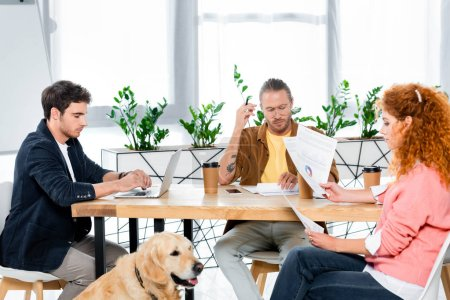Photo for Three friends sitting at table and doing paperwork in office - Royalty Free Image