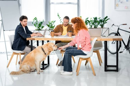 two friends working and woman feeding cute golden retriever
