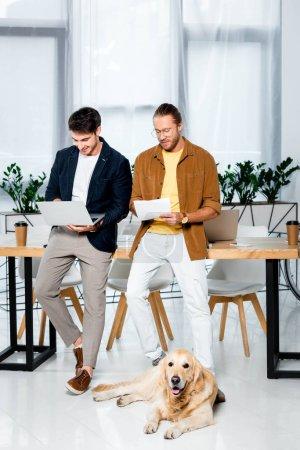 Foto de Dos amigos guapos haciendo papeleo y golden retriever acostado en el suelo en la oficina - Imagen libre de derechos