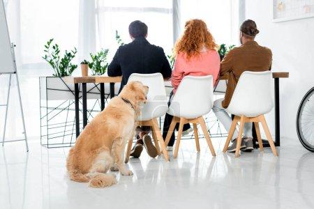 Photo pour Vue arrière de trois amis s'asseyant à la table et retriever d'or s'asseyant sur l'étage - image libre de droit