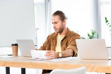 Photo pour Bel homme faisant de la paperasse et regardant ordinateur portable - image libre de droit