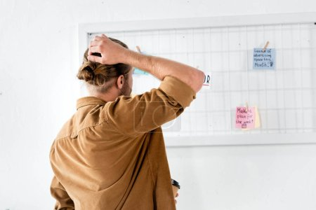 Photo for Back view of man in shirt looking at white board in office - Royalty Free Image