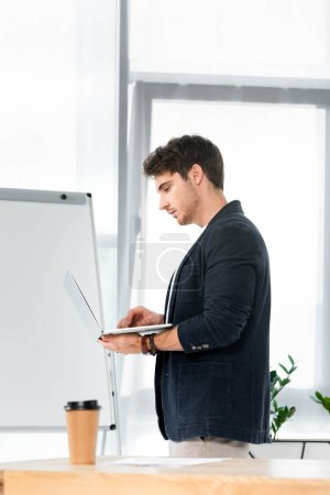 Photo for Side view of handsome in shirt using laptop in office - Royalty Free Image