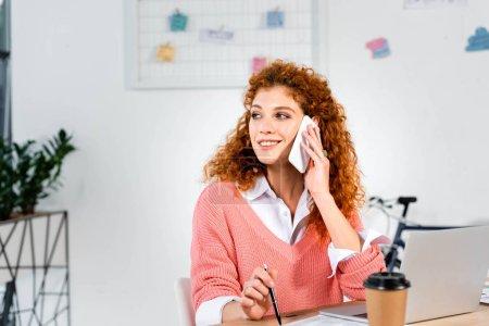 Photo pour Femme d'affaires attirante et souriante dans le chandail rose parlant sur le smartphone dans le bureau - image libre de droit