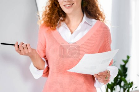 Photo for Cropped view of smiling businesswoman in pink sweater holding paper and pen - Royalty Free Image