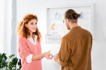 Photo pour Femme d'affaires attrayante dans le chandail rose parlant et donnant la carte à son ami - image libre de droit