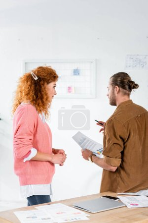 Photo for Back view of two friends talking and doing paperwork in office - Royalty Free Image