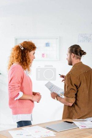 Foto de Vista trasera de dos amigos hablando y haciendo el papeleo en la oficina - Imagen libre de derechos
