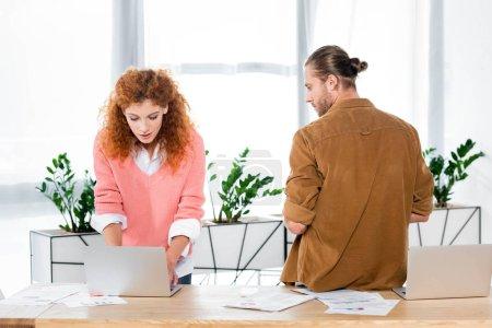 Photo pour Femme attirante utilisant l'ordinateur portatif et l'homme regardant son - image libre de droit