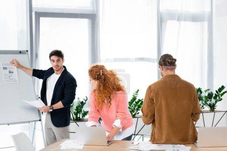 Photo pour Gens d'affaires regardant un ami montrant du papier avec des cartes et des graphiques - image libre de droit
