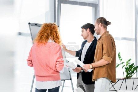 Photo pour Trois amis faisant de la paperasse et regardant flipchart dans le bureau - image libre de droit