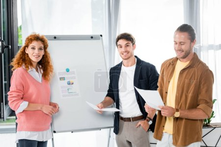 Photo for Three smiling friends holding papers near flipchart and looking at camera in office - Royalty Free Image