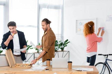 Photo pour Trois amis souriants mangeant la pizza et faisant la paperasse dans le bureau - image libre de droit