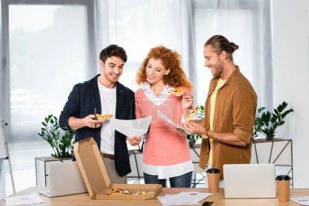 Photo pour Trois amis de sourire retenant des tranches de pizza et faisant la paperasse dans le bureau - image libre de droit