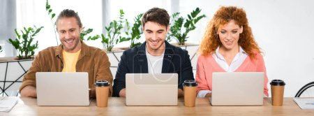 Photo for Panoramic shot of three smiling friends using laptops in office - Royalty Free Image