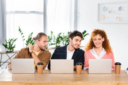 Photo pour Trois amis souriants assis à table et utilisant des ordinateurs portables dans le bureau - image libre de droit