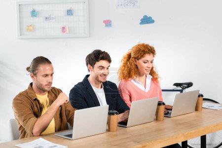 Photo pour Trois amis de sourire s'asseyant à la table et utilisant des ordinateurs portatifs dans le bureau - image libre de droit