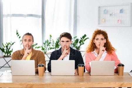 Photo pour Trois amis assis à table et montrant ses gestes au bureau - image libre de droit