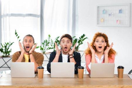 Photo pour Trois amis choqués assis à table et regardant la caméra - image libre de droit