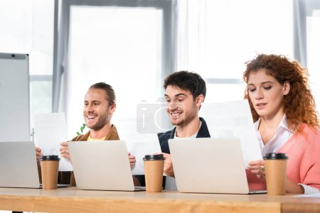 three smiling friends sitting at table and doing paperwork