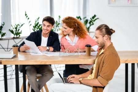 Photo for Three smiling friends doing paperwork and using laptop in office - Royalty Free Image