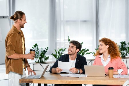 Photo for Three smiling friends doing paperwork and talking in office - Royalty Free Image