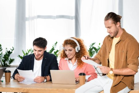 three smiling friends doing paperwork and using laptop in office