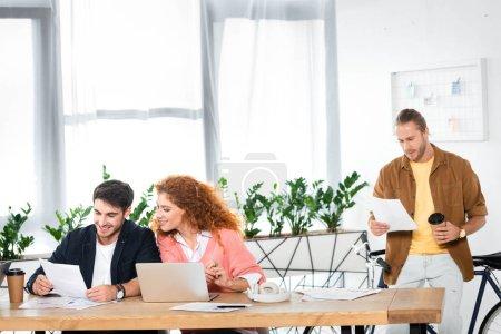Foto de Tres amigos sonrientes haciendo el papeleo y sentado en la mesa en la oficina - Imagen libre de derechos