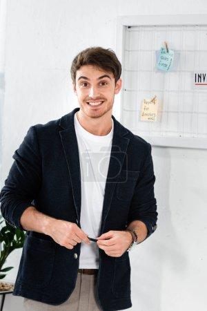 Photo pour Homme souriant et beau dans la chemise regardant l'appareil-photo dans le bureau - image libre de droit
