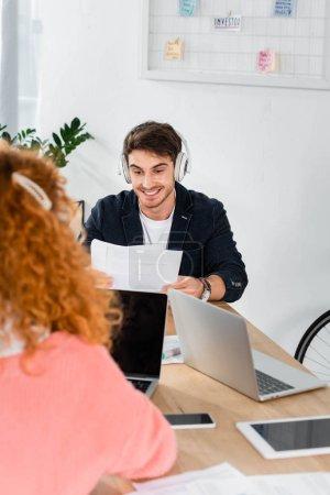 Photo pour Foyer sélectif de sourire et bel homme dans le casque utilisant l'ordinateur portatif - image libre de droit