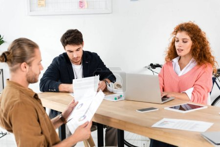 Photo for Three friends doing paperwork and using laptop in office - Royalty Free Image
