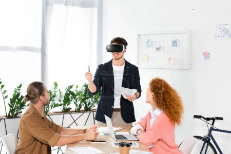 Photo for Smiling businessman with virtual reality headset holding pen and papers and friends looking at him - Royalty Free Image