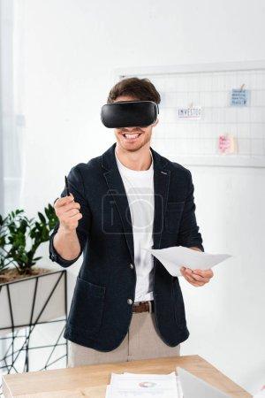 Photo pour Homme d'affaires de sourire dans la chemise avec le stylo et les papiers de fixation de casque de réalité virtuelle - image libre de droit