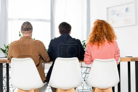 Photo for Back view of three friends sitting in chairs in office - Royalty Free Image