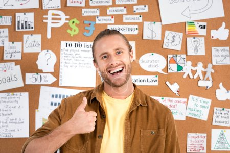 Photo for Handsome and smiling businessman in shirt showing thumb up in office - Royalty Free Image