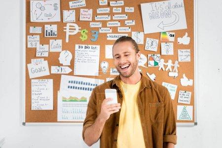 Foto de Guapo y sonriente hombre de negocios en la camisa usando el teléfono inteligente en la oficina - Imagen libre de derechos