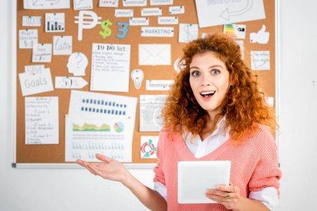 Photo pour Femme d'affaires attirante et choquée dans le chandail rose retenant la tablette numérique - image libre de droit