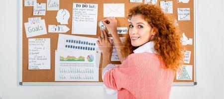 Photo pour Tir panoramique de femme d'affaires attirante dans la carte rose de mise de chandail sur la planche en bois - image libre de droit