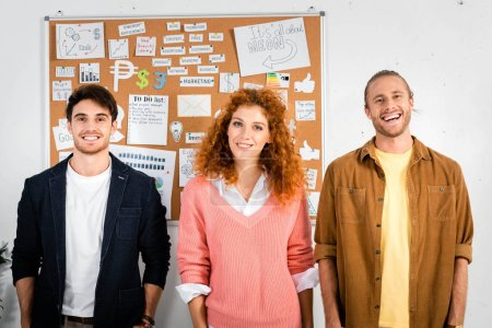 Photo for Three friends smiling and looking at camera in office - Royalty Free Image