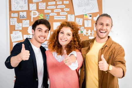 Photo for Three smiling friends showing thumbs up and looking at camera - Royalty Free Image