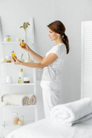 Photo pour Focus sélectif des huiles attrayantes de parfum de fixation de masseur dans des bouteilles - image libre de droit
