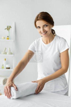 Photo pour Attrayant et souriant masseur tenant serviette blanche dans le spa - image libre de droit