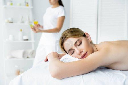 Photo pour Femme attirante avec les yeux fermés se trouvant sur le tapis de massage dans le spa - image libre de droit