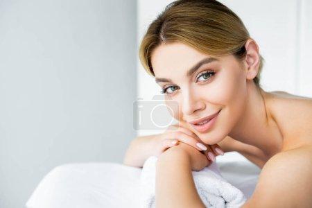 Photo pour Femme attirante et souriante se trouvant sur le tapis de massage dans le spa - image libre de droit