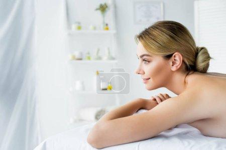 Photo pour Vue de côté de femme attirante et souriante se trouvant sur le tapis de massage dans le spa - image libre de droit