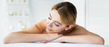 Photo pour Tir panoramique de la femme attirante avec les yeux fermés se trouvant sur le tapis de massage dans le spa - image libre de droit